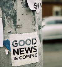 sign on light pole indicating good news is coming